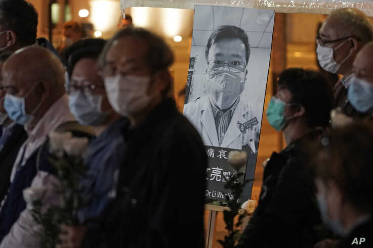 People wearing masks, attend a vigil for Chinese doctor Li Wenliang, in Hong Kong, Friday, Feb. 7, 2020. The death of a young…