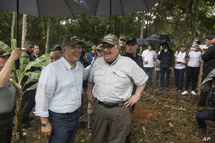 In this Jan. 29, 2020 photo, Colombia's President Ivan Duque, left, and Howard Buffet share a laugh during a tour of a cocoa…