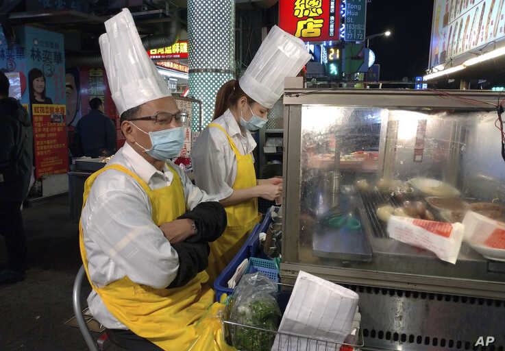 Two vendors wear face masks and wait for customers at a night market in Taipei, Taiwan, Thursday, Feb. 6, 2020. According to…