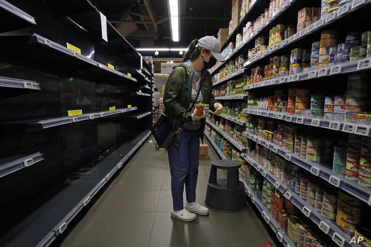A woman wearing face mask and gloves buys canned foods besides empty shelves, at a supermarket in Hong Kong, Thursday, Feb. 13,…