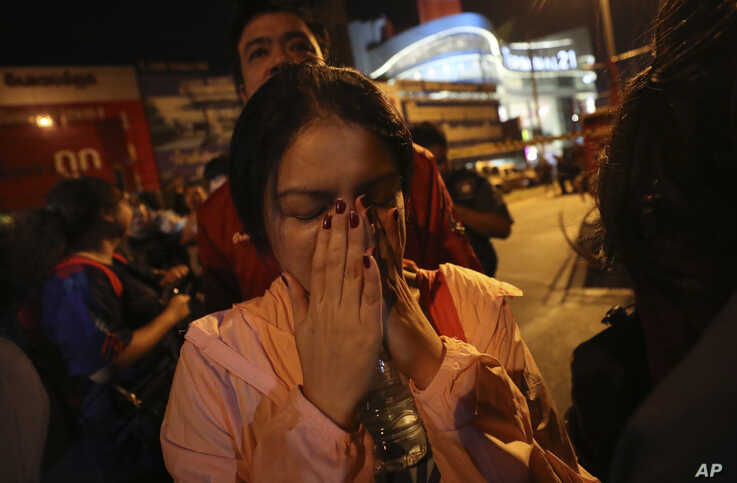 A woman who was able to get out of Terminal 21 Korat mall gestures with her hands on her face in Nakhon Ratchasima, Thailand on…
