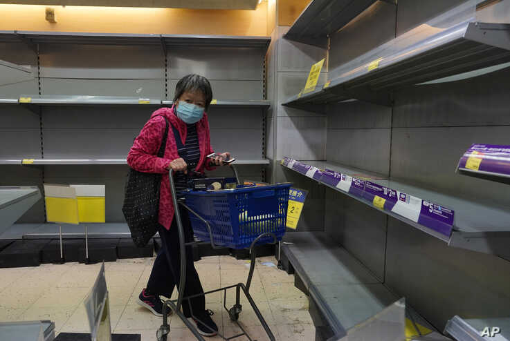 A woman wearing face mask walks past empty shelf of tissue papers at a supermarket in Hong Kong, Thursday, Feb. 6, 2020. Ten…