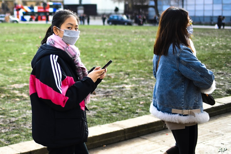 Two women in masks walk in Parliament Square, in London, Saturday, Feb. 1, 2020. Two cases of coronavirus have been confirmed…