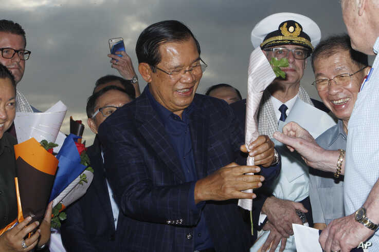 Cambodia's Prime Minister Hun Sen, center, gives a flower to a passenger who disembarked from the MS Westerdam, owned by…