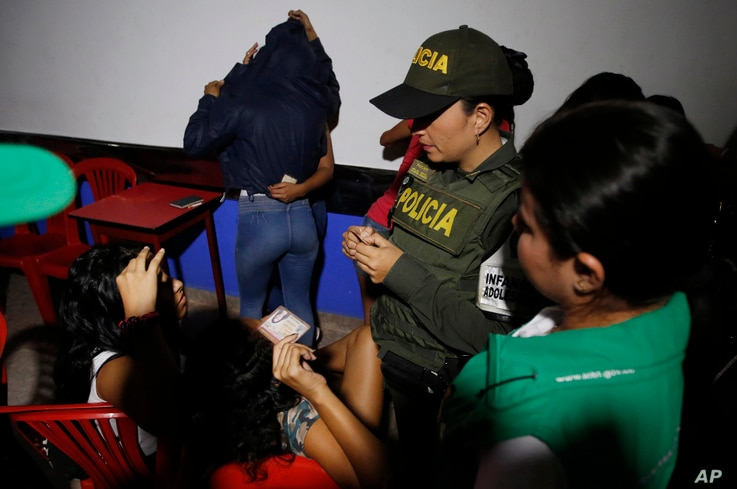 In this June 26, 2018 photo, police look at the identification cards of Venezuelan girls to check their ages as they search for…