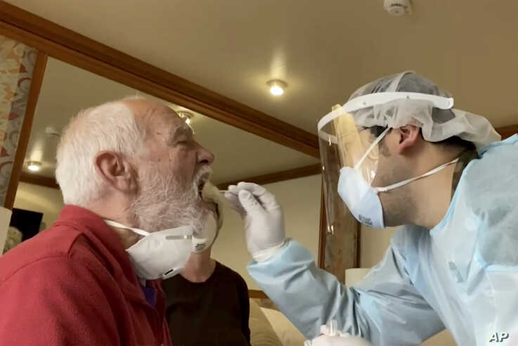 In this image from a video, Paul Molesky, left, gets a DNA swab test in his cabin room on the Diamond Princess, anchored at a…