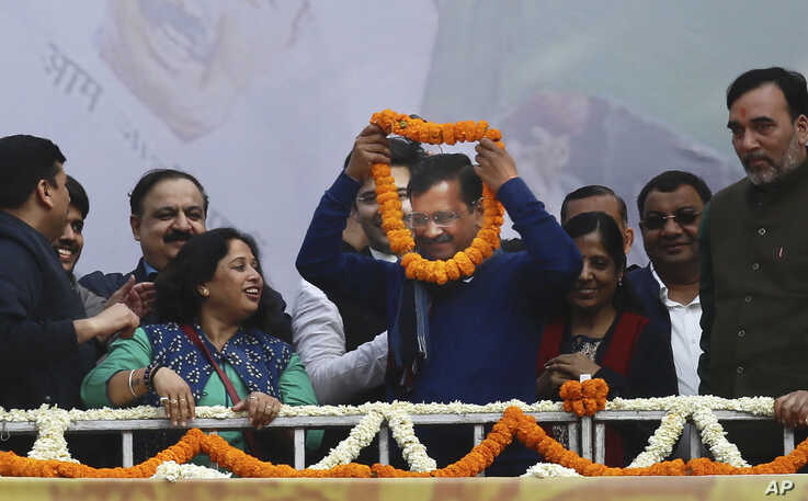 """Incumbent Delhi Chief Minister Arvind Kejriwal, center, is garlanded at Aam Aadmi Party, or """"common man's"""" party headquarters…"""