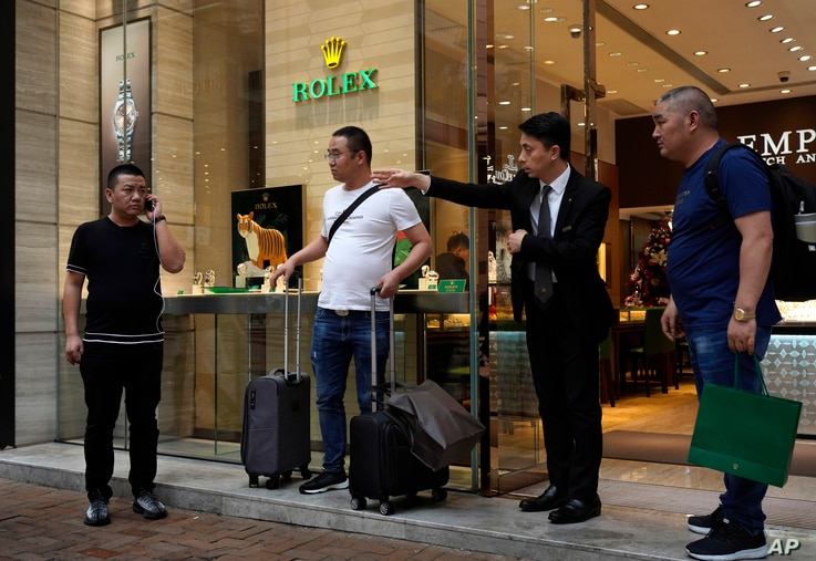 In this Oct. 30, 2019, photo, a salesman of a watch shop directs the way to find a taxi for a group of mainland tourists in a…