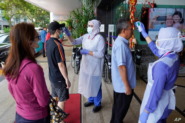 FILE - In this Feb. 5, 2020, file photo, nurses check the temperatures of visitors as part of the coronavirus screening…