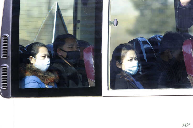 FILE - In this Feb. 26, 2020, file photo, people wear masks as they ride on a public bus in Pyongyang, North Korea. As a new…