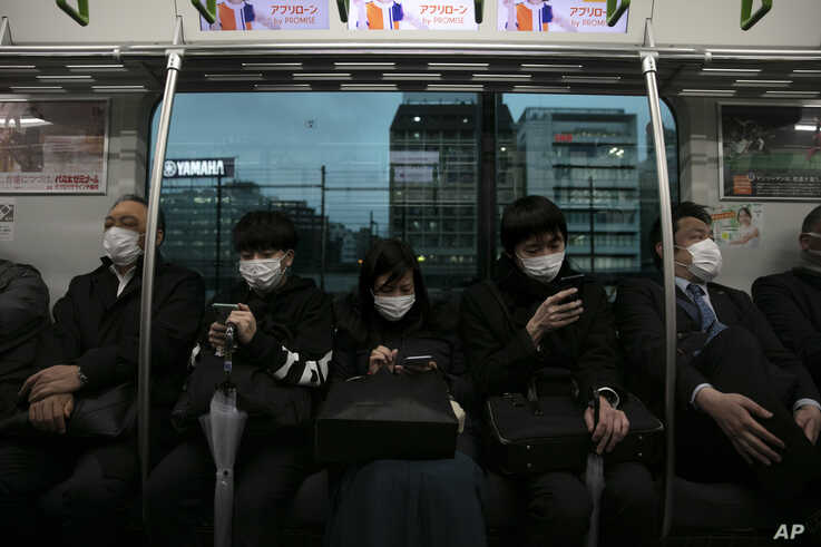 Commuters wearing masks sit on a train in Tokyo, Monday, March 2, 2020. Coronavirus has spread to more than 60 countries, and…