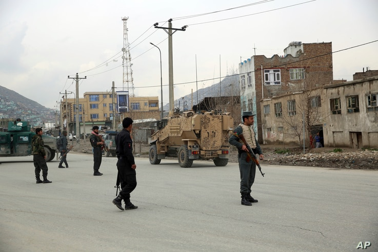 Afghan security personnel and British soldiers with NATO-led Resolute Support Mission forces arrive at the site of an attack in…