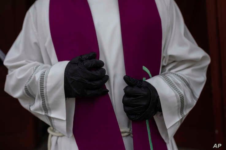 A priest wearing a gloves to protect against coronavirus waits in front the cemetery chapel during the coronavirus outbreak in…