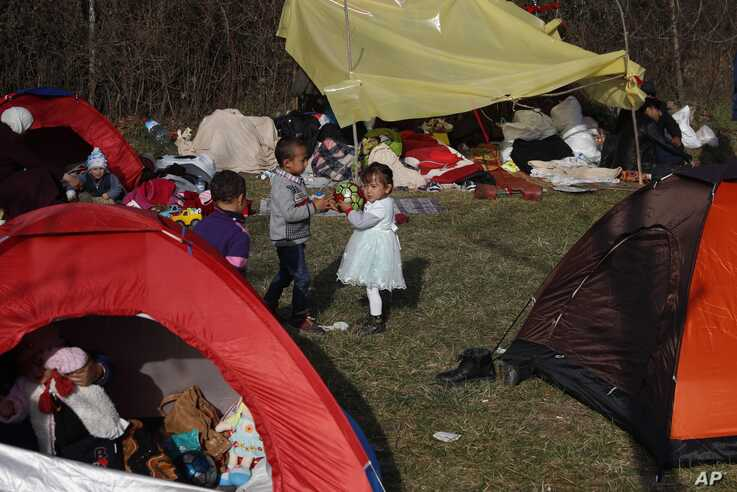 Children play as migrants gather in a field in Edirne, near the Turkish-Greek border on Sunday, March 8, 2020. Thousands of…