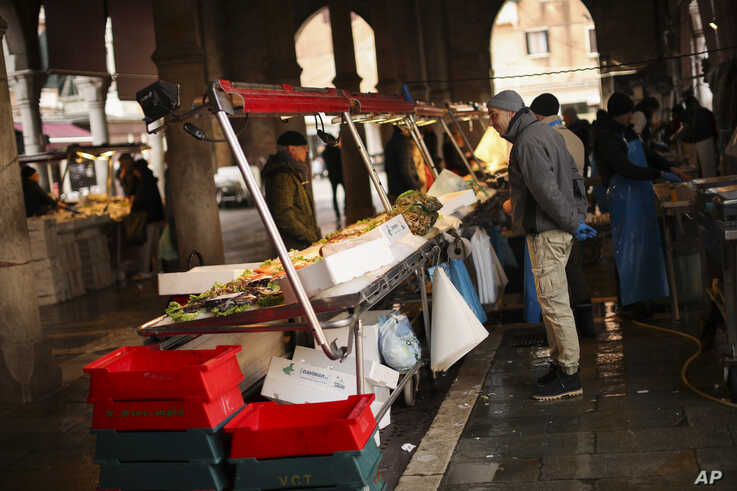 A fishmonger waits for customers in a barely empty street food market in Venice, Saturday, Feb. 29, 2020. A U.S. government…