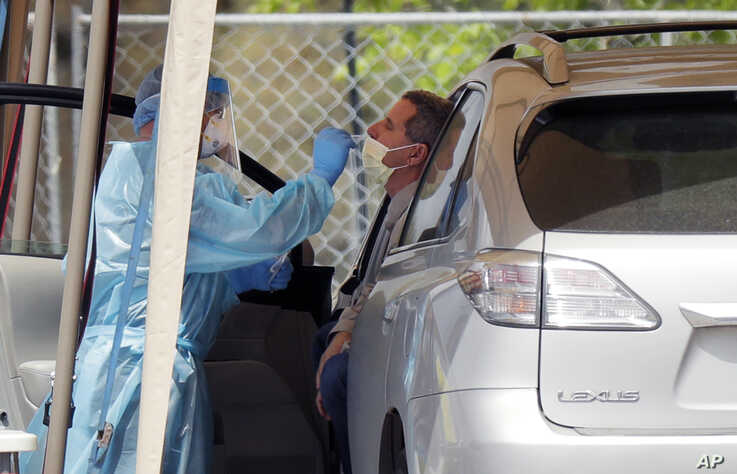 A medical worker tests a person for the coronavirus at a drive-through facility primarily for first responders and medical…