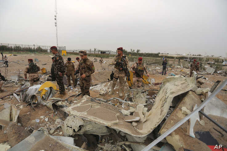 Iraqi army soldiers inspect the destruction at an airport complex under construction in Karbala, Iraq, Friday, March 13, 2020…