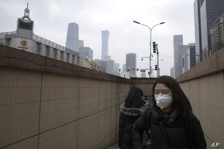 Residents walk out of a subway station near the central business district in Beijing Monday, March 9, 2020. With almost no new…