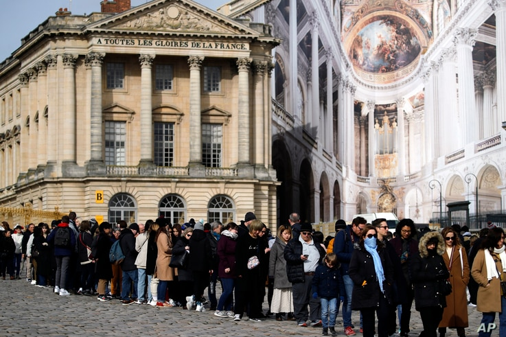 Visitors stand in line to enter the Chateau de Versailles, west of Paris, Tuesday, March 3, 2020. The Chateau de Versailles…