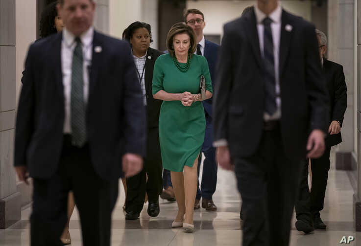 Flanked by her security detail and aides, Speaker of the House Nancy Pelosi, D-Calif., arrives to update reporters as lawmakers…
