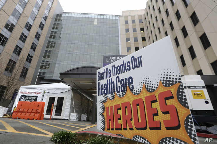 A sign posted in front of the emergency entrance of Harborview Medical Center gives thanks to health care workers during the…