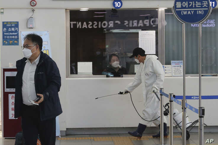 A worker sprays disinfectant as a precaution against the new coronavirus at the Seoul Railway Station in Seoul, South Korea,…