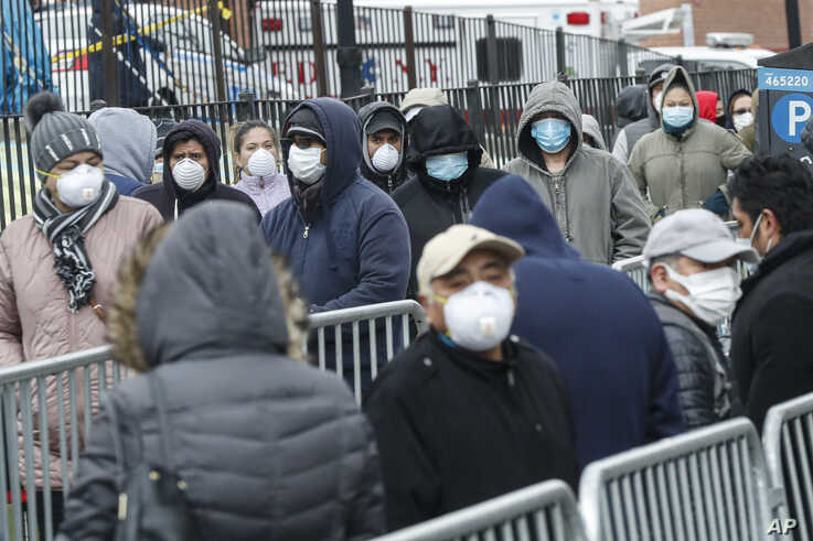 Patients wear personal protective equipment while maintaining social distancing as they wait in line for a COVID-19 test at…