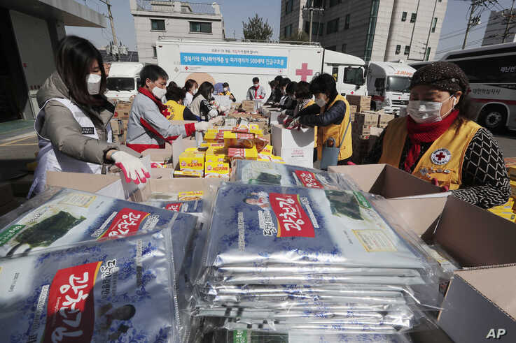 Red Cross workers prepare emergency relief kits packed with basic necessities like instant food for delivery to impoverished…