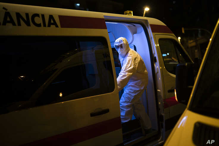 An emergency worker wearing a protective suit closes the door of an ambulance transferring a COVID-19 patient in Barcelona,…