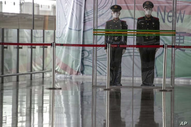 In this March 12, 2020, photo, Chinese paramilitary policemen stand on duty behind a barrier at the Capital International…