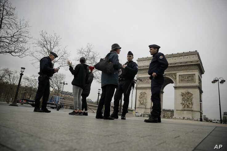 Police officers control on the Champs-Elysees avenue Tuesday, March 17, 2020 in Paris. French President Emmanuel Macron said…