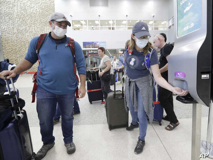 Linda Scruggs, right, applies hand sanitizer as Mike Rustici, left, watches after they arrived on a flight from Lima, Peru,…
