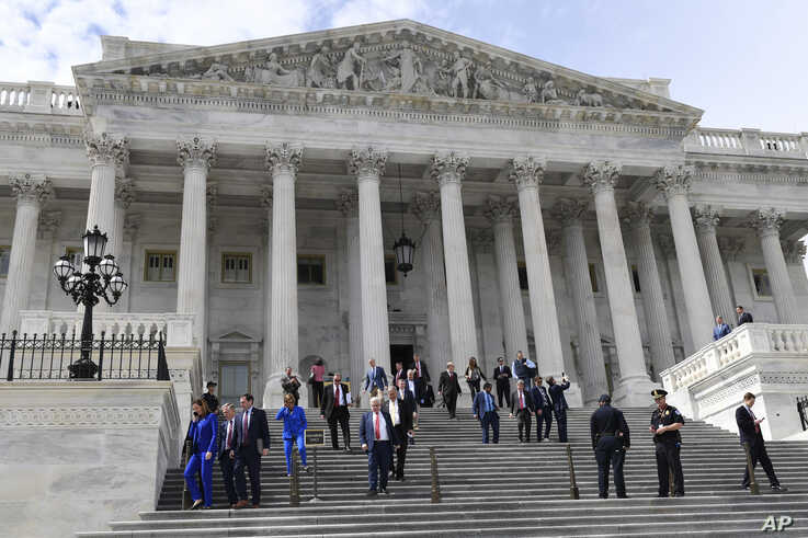 Members of the House of Representatives walk down the steps of Capitol Hill in Washington, Friday, March 27, 2020, after…