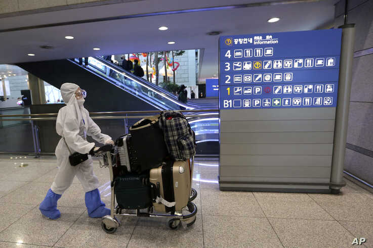 A Chinese woman wearing a protective gear moves as she waits for her flight at the Incheon Airport in Incheon, South Korea,…