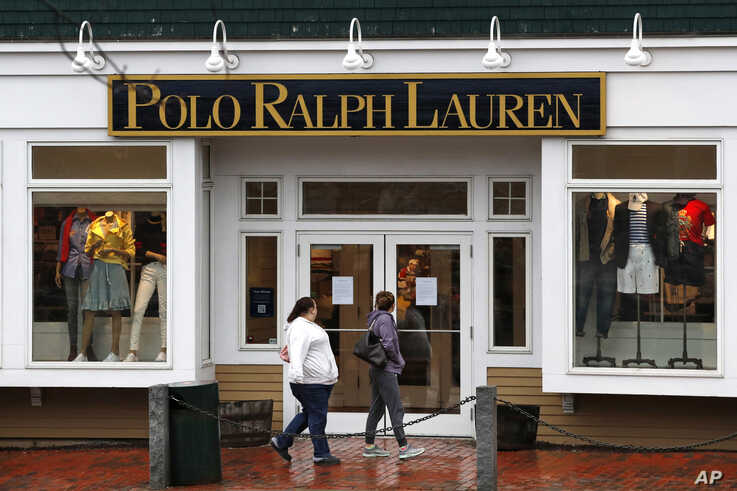 Women read a notice announcing the temporary closure of a Polo Ralph Lauren store, Tuesday, March 17, 2020, in Freeport, Maine…