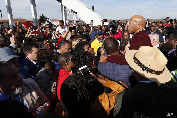 U.S. Rep. John Lewis speaks to the crowd as they cross the Edmund Pettus Bridge, Sunday, March 1, 2020, in Selma, Ala. (AP…