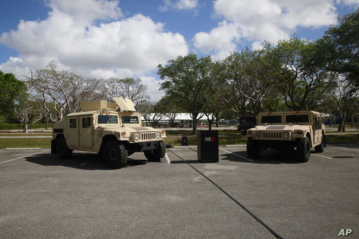 Vehicles are parked in front of where the National Guard is preparing for drive-through COVID-19 testing at C.B. Smith Park on…