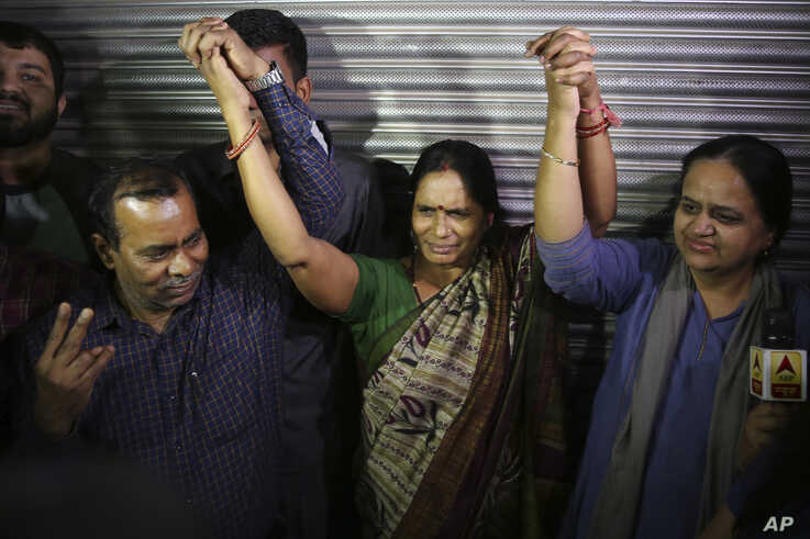Badrinath, left, Asha Devi, center, parents of the victim of the fatal 2012 gang rape on a moving bus, hold hands as they react…