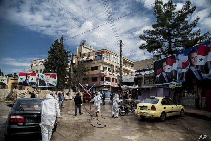 Workers disinfect the streets to prevent the spread of coronavirus in Qamishli, Syria, Tuesday, March 24, 2020. Posters show…