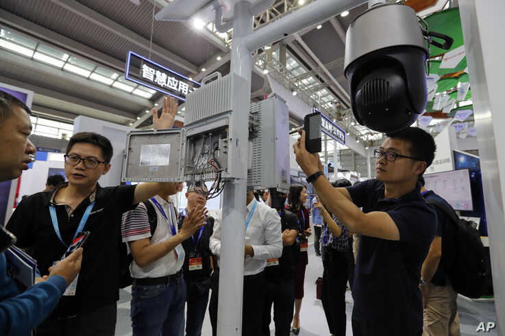 In this Tuesday, Oct. 29, 2019, photo, visitors look at the 5G mobile station and a surveillance camera by China's telecoms…