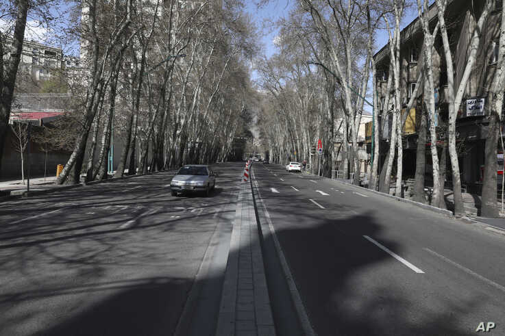 Cars drive in Vali-e-Asr St. which usually has congested traffic in northern Tehran, Iran, Friday, March 20, 2020, on the first…