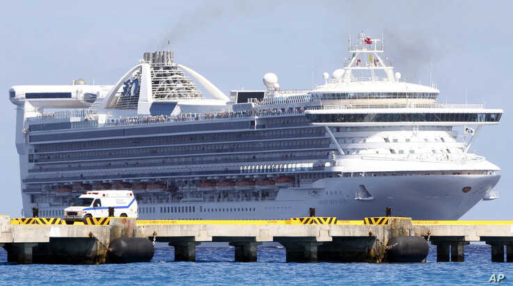 An ambulance waits at a dock upon the arrival of the cruise ship Grand Princess as it arrives in the port of Mahaual, Mexico,…