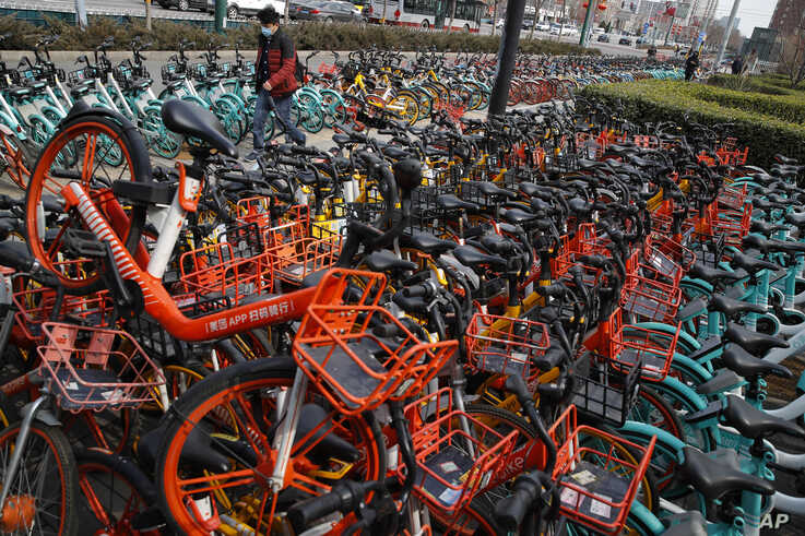 A man wearing a protective face mask walks by a pile of bicycles from bike-sharing companies parked outside a subway station in…