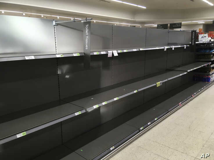 Shelves stand empty in the aisle for toilet rolls, after panic buying as result of the coronavirus, in a branch of the Waitrose…
