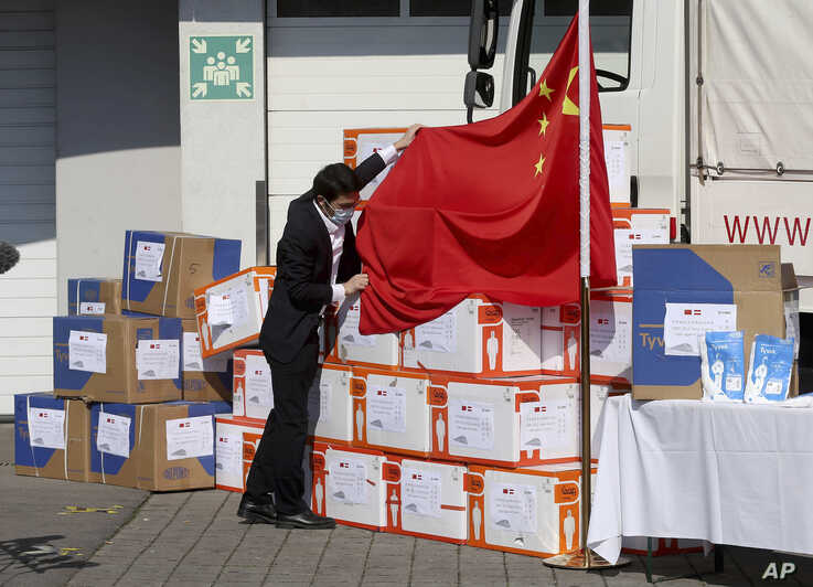 A man fixes the chinese flag in front of boxes with Protective suits and masks in Vienna, Austria, Friday, March 20, 2020…