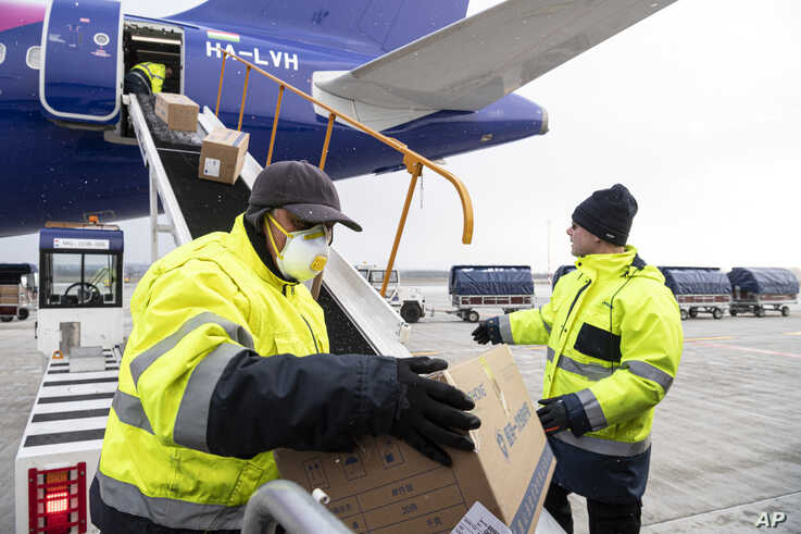 Workers unload boxes containing medical aid and protective materials to combat the COVID-19 coronavirus from a plane of the…