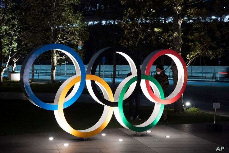 Two men chat behind the Olympic rings near the New National Stadium in Tokyo, Tuesday, March 24, 2020. IOC President Thomas…