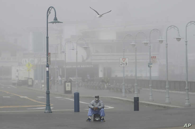 A street performer sits alone at Fisherman's Wharf in San Francisco, Thursday, March 12, 2020.  California Gov. Gavin Newsom…