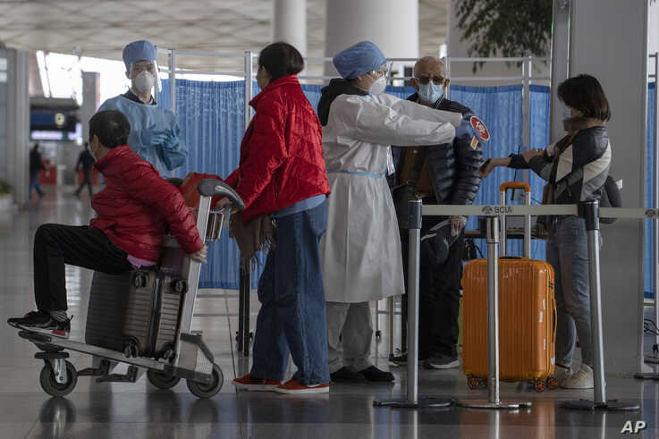 In this March 12, 2020, photo, health workers screen people entering the Capital International Airport terminal 3 in Beijing. …