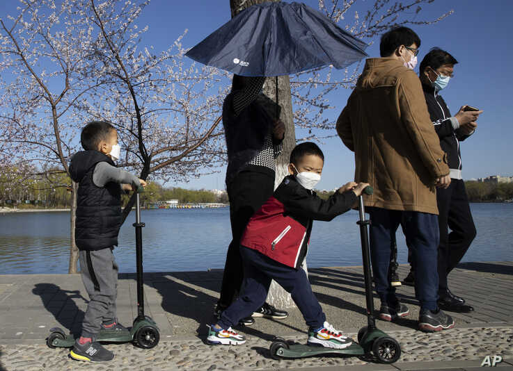 Visitors wear masks as they enjoy the sights at a park during a sunny day in Beijing on Thursday, March 19, 2020. China has…
